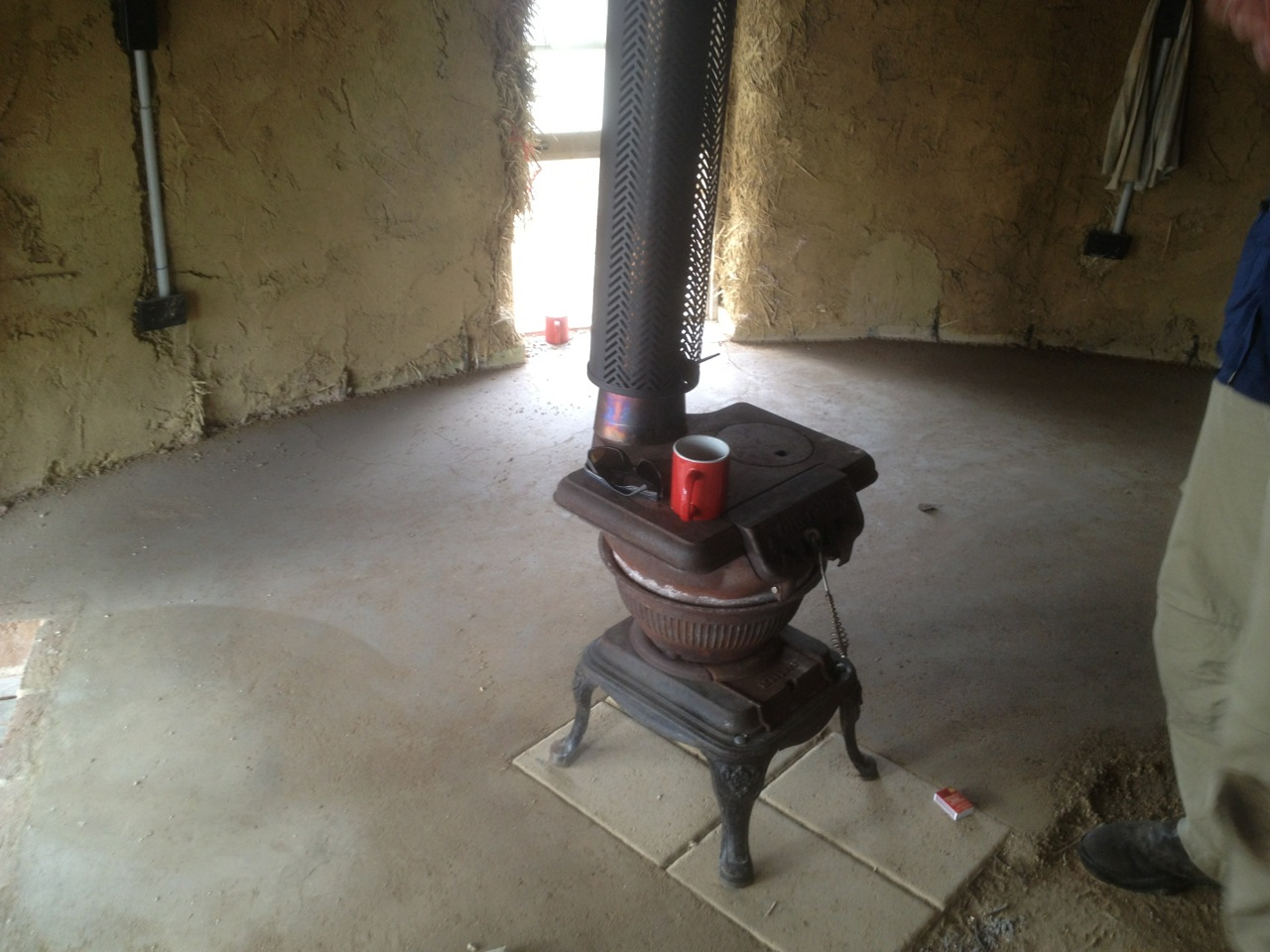 Roundhouse build: the stove is in! And check out that earth floor - it's nearly done too...